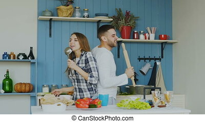 Slowmotion of Young joyful couple have fun dancing and singing while cooking in the kitchen at home
