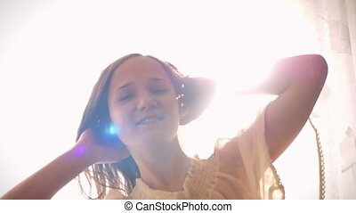 Slowmotion of young smiling woman is cheering a new day, dancing, stretching and smiling on the background of sunlight in the morning and catches the sun