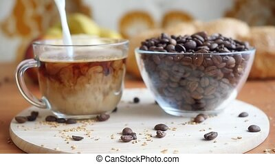Slowmotion pouring milk in a transparent coffee cup and take it.  The coffee beans on the table