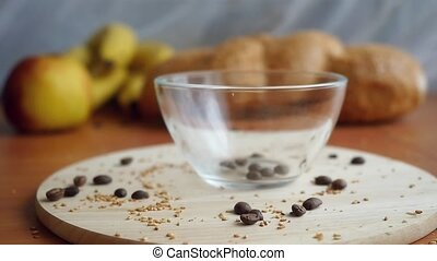 Slowmotion putting the coffee beans in a transparent Coffee cup