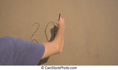 Slowmotion shot. A man writes 2021 on the sand on a beach. Concept of changes in life. Change of the years.