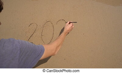 Slowmotion shot. A man writes 2021 on the sand on a beach. Concept of changes in life. Change of the years