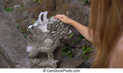 Slowmotion shot of a beautiful young woman visiting the Puri Saren Royal Palace in Ubud village on the Bali Island. Travel to Indonesia concept