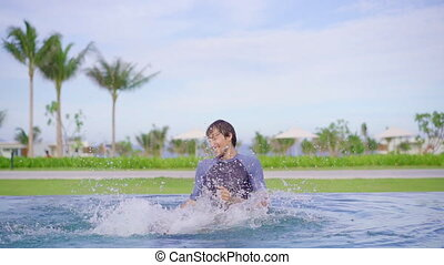 Slowmotion shot of a father and son that are having fun in a swimming pool.