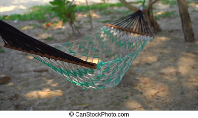 Slowmotion shot of a hammock on a tropical beach.