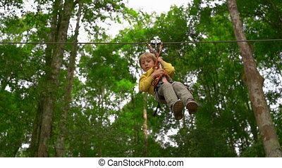 Slowmotion shot of a little boy in a safety harness on a...