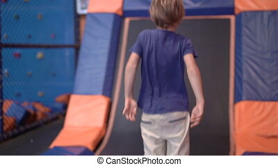 Slowmotion shot of a little boy in a trampoline amusement center
