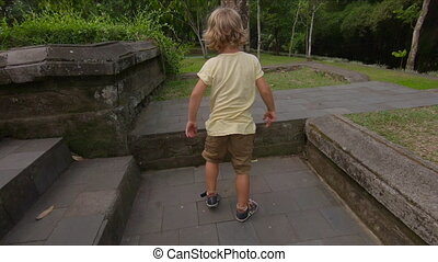Slowmotion shot of a little boy jumping and making a 180...