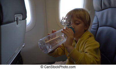 Slowmotion shot of a little boy that drinks water from the...