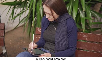 Slowmotion shot of a woman drawing on digital tablet with stylus pencil