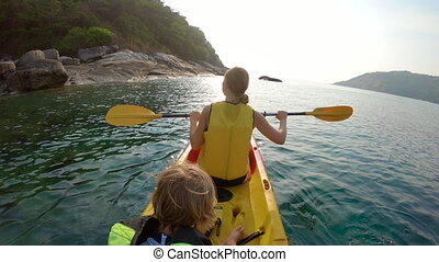 Slowmotion shot of a young family kayaking in a tropical sea...