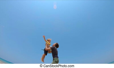 Slowmotion shot of a young father throwing son in the air...