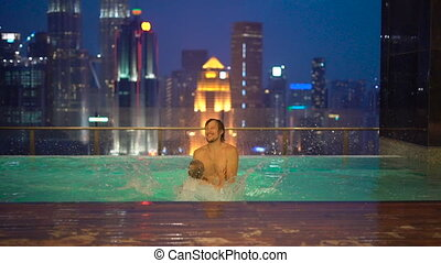 Slowmotion shot of a young man and his little son having fun in a rooftop water pool with view on skyscrapers