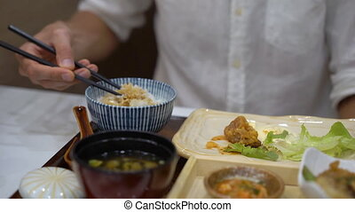 Slowmotion shot of a young man eatimg asian food in...