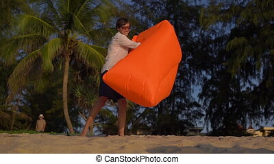 Slowmotion shot of A Young Man Inflates An Inflatable Sofa on a beautiful beach