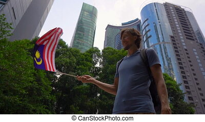 Slowmotion shot of a young man that holds a smartphone and waves Malaysian flag with skyscrapers at a background. Travel to Malaysia concept