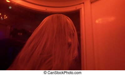 Slowmotion shot of a young woman in a storm wind chamber in...
