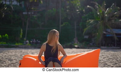 Slowmotion shot of a young woman on a tropical beach sitting on an inflatable sofa. Summer vacation concept