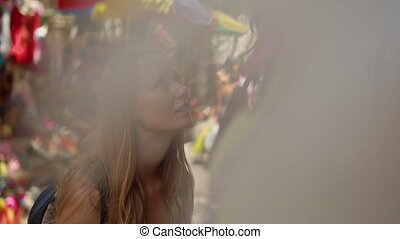 Slowmotion shot of a young woman traveler visiting an Asian marketplace choosing the souvenir