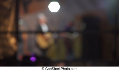 Slowmotion shot of silhouettes of people in a crowd on the background of the stage at a concert