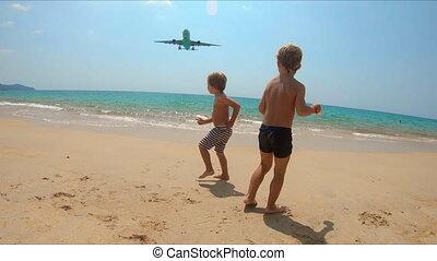 slowmotion shot of two kids having fun on the beach watching...