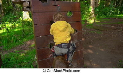 Slowmotion shot of two little boys in a safety harness in a...