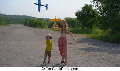 Slowmotion shot of young woman and her son playing with a polystyrene airplanes