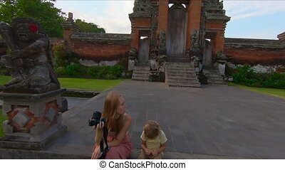 Slowmotion steadicam shot of a young woman and her little...