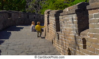 Slowmotion steadicam shot of the China Great wall that rises up the side of the mountain. A young woman and her little son take a break on the stairs of the Wall