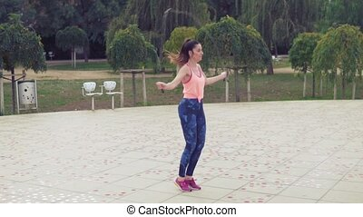 Fit beautiful woman with jumping rope in a park - Slowmotion...
