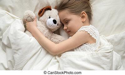 Slumber kid embrace stuffed toy sleeping in bed top view