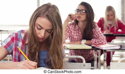 Shifting focus from student to student, close up of girl putting down information and boy taking a nap at lecture