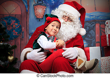 sly elf - Santa Claus sitting with a little cute boy elf ...