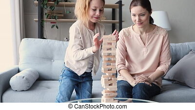Overjoyed young mother celebrating win when little preschool redhead daughter ruined wooden tower. Small 7 years old adorable child girl failed in board game, having fun with mum indoors.