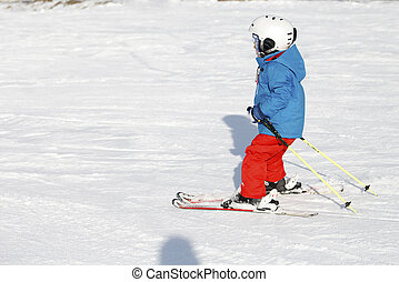 small active child skiing on snow slope