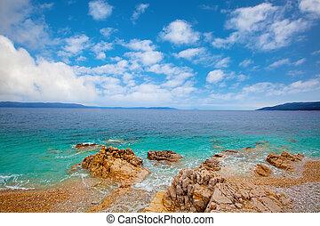Small Adriatic coastline Croatia. Clear azure water under blue sky.