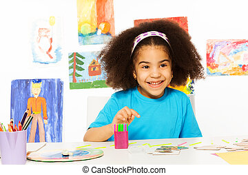 Small African girl sits at the table with puzzle