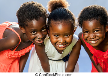 Small african girls joining heads. - Close up portrait of...