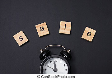 Small alarm clock and word Sale on black background
