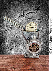 Small alarm clock in meat grinder on grunge monochrome backgroun