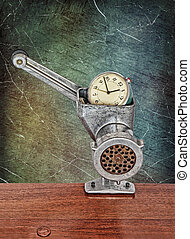 Small alarm clock in meat grinder on grunge scratched background.
