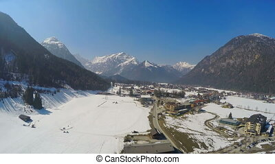 """Small Alpine resort town at lakeside, huge mountains, snowy..."