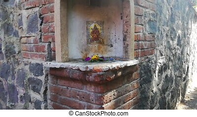 Close-up of small religious altar on corner of brick and stone wall. Flowers and religious image on wall from alley in Mexico City. Mexican culture and religions