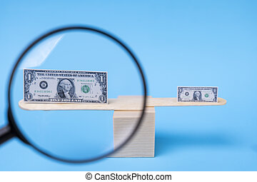 Small and large 1 dollar bill on scales. Looking through a magnifying glass