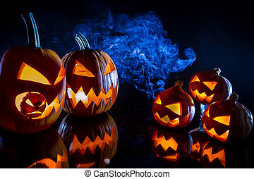 Small and large pumpkins for Halloween with candles on a black background