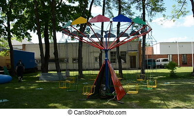 small and primitive carousel in the urban square