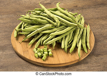 small and slender green beans (haricot vert) on a wood. Fresh vegetable.