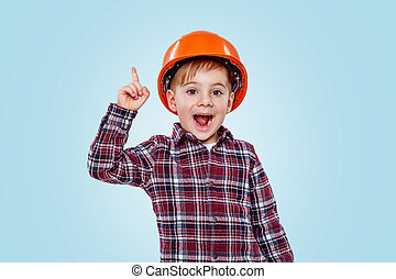 Small architect boy with helmet pointing up to copy space