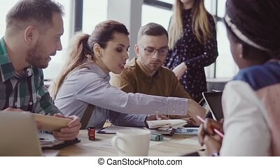 Small architectural company working at project. Creative business meeting of young mixed race team in modern office. Attractive people sitting at the table and discussing, talking together.