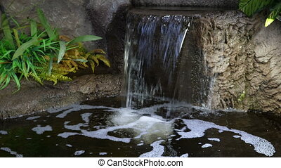 Small artificial waterfall in the park